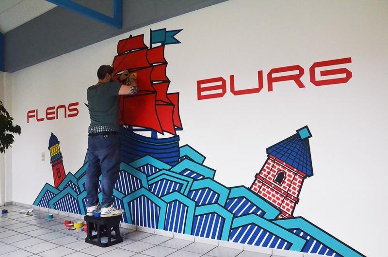 Flensburg- Kleben an der Wand- Tape Graffiti Auftrag- Künstler bei der Arbeit